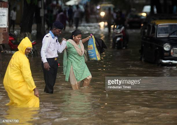 Security guard help a girl to walks through a flooded street during heavy rain at Parel on June 7 2015 in Mumbai India According to Weather bureau...