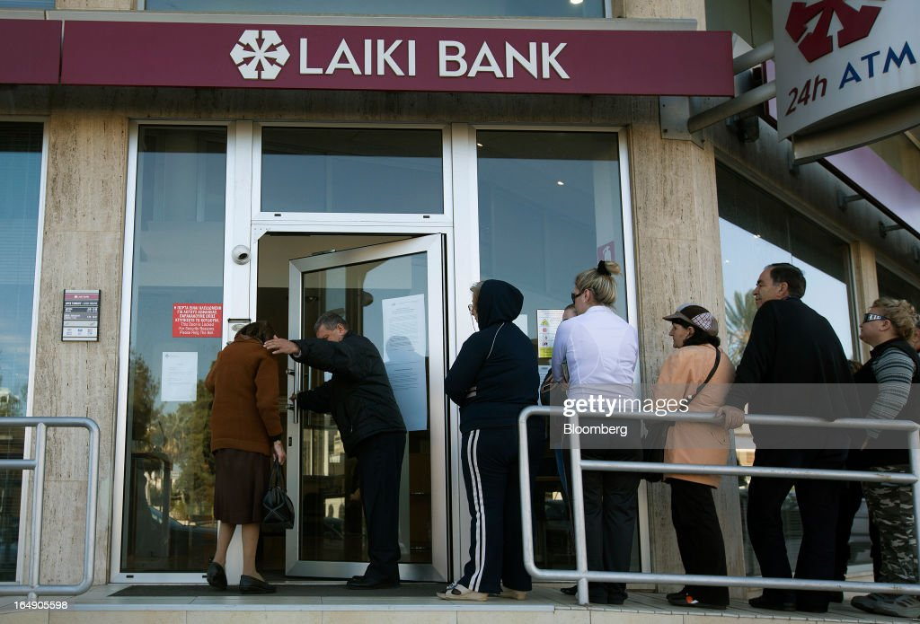 A security guard helps the first customer of the day, an elderly lady, left, enter a branch of a Cyprus Popular Bank Pcl, also known as Laiki Bank, as others wait their turn in Nicosia, Cyprus, on Friday, March 29, 2013. Cypriots face a second day of bank controls over their use of the euro as officials in Europe urged the country to move quickly to lift the restrictions, the first time they have been imposed on the common currency. Photographer: Simon Dawson/Bloomberg via Getty Images
