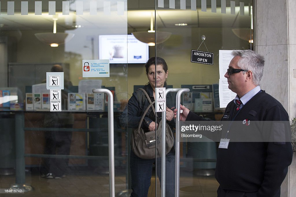 A G4S security guard holds the door open as a customer exits a Bank of Cyprus Plc branch as banks open for the first time in two weeks in Nicosia, Cyprus, on Thursday, March 28, 2013. The Central Bank of Cyprus's capital controls will include a 300-euro ($383) daily limit on withdrawals and restrictions on transfers to accounts outside the country. Photographer: Simon Dawson/Bloomberg via Getty Images