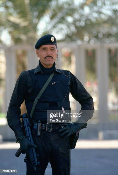 A security guard in the ruler's special protection force with earpiece connected to a twoway radio holding a machine gun He is wearing a bulletproof...