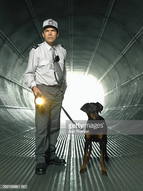 Security guard in tunnel with dog and illuminated torch