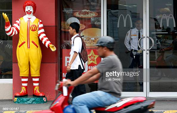 CITY PHILIPPINES – JULY 21 2009 A security guard keeps a watchful eye out the glass doors of a McDonald's franchise in Zamboanga City Philippines...