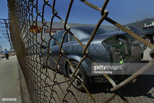 A security guard left makes his way past the lot as a car awaiting body repair sits behind a locked barbed wire fence at a M2 Collision Care Centers...