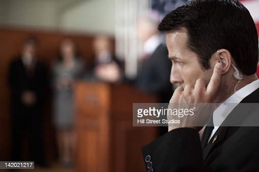 Security guard listening to earpiece at public speech