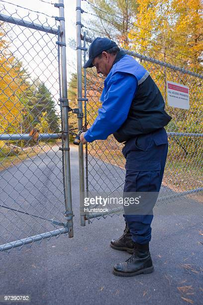 Security guard locking a gate at water treatment facility