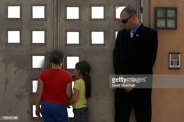 A security guard looks on as Israeli schoolgirls Naveh Mesilatti and Adi Mesilatti ask to be allowed into the house where film star Leonardo DiCaprio...