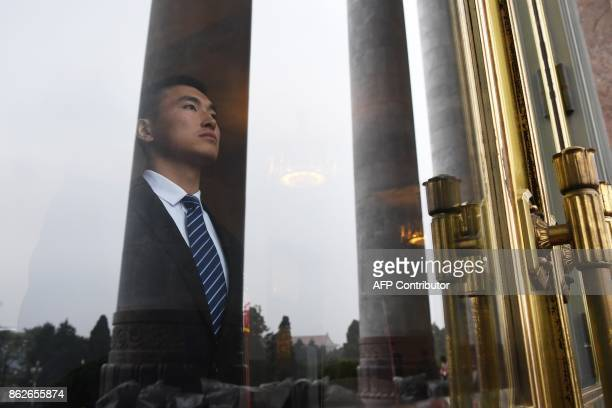 A security guard looks out from an entrance to the Great Hall of the People during the opening ceremony of the 19th Communist Party Congress in...
