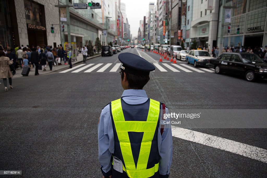 A security guard looks over a road on May 02, 2016 in the Ginza area of Tokyo, Japan. The Greater Tokyo Area is the most populous metropolitan area in the world with a population of 13,506,607 and is currently ranked first in the world in the Safe Cities Index.