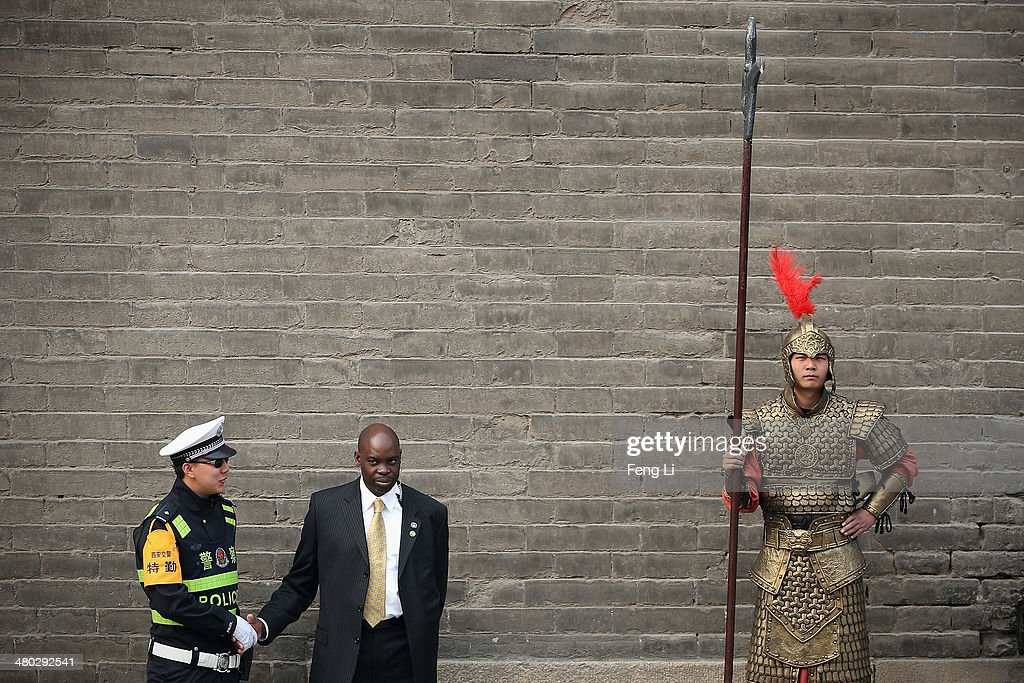 A security guard of U.S. first lady Michelle Obama shakes hands with a Chinese policeman as he standing beside a man wearing a Chinese ancient warrior costume during Obama's visit at the City Wall on March 24, 2014 in Xi'an, China. Michelle Obama's one-week-long visit in China will be focused on educational and cultural exchanges.
