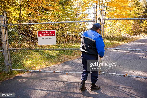 Security guard opening a gate to water protection area