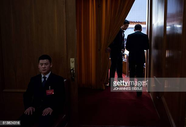 A security guard opens a curtain to let a man pass by during the opening ceremony of the National People's Congress in the Great Hall of the People...