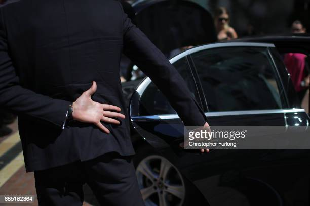 A security guard opens the car door for a celebrity outisde a hotel on the Boulevard de la Croisette during the Cannes Film Festival on May 19 2017...