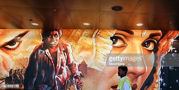 A security guard passes a mural as he walks along a moving walkway inside the newly built Terminal 2 of the Chhatrapati Shivaji International Airport...