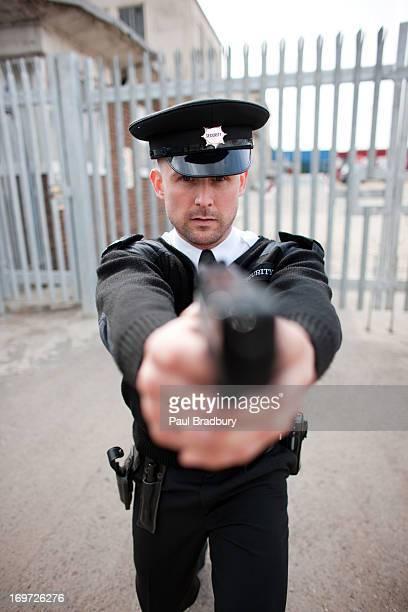Security guard pointing gun