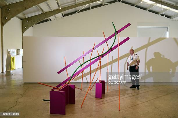 A security guard poses for a photograph alongside a sculpture entitled 'Month of May' by artist Sir Anthony Caro as it stands on display as part of...