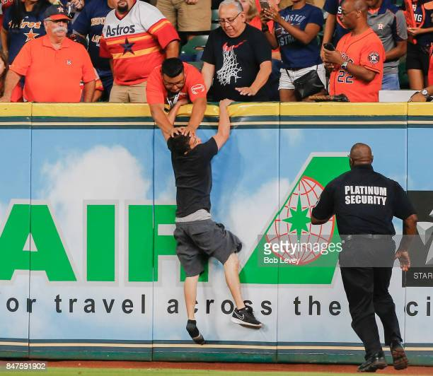 A security guard pushes a fan back onto the warning track after he ran onto the field in the first inning during the game between the Seattle...
