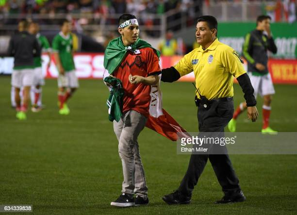 A security guard removes a fan who ran onto the field after Mexico defeated Iceland 10 in an exhibition match at Sam Boyd Stadium on February 8 2017...