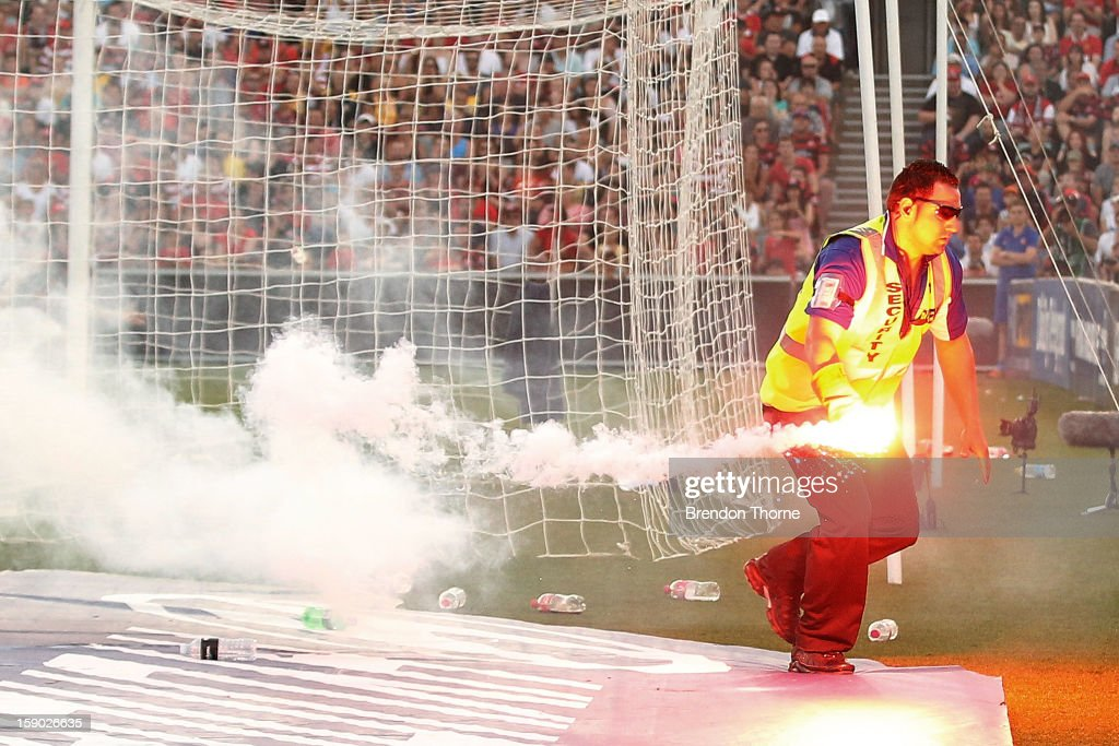 A security guard removes a flare from the playing field during the round 15 A-League match between the Western Sydney Wanderers and the Central Coast Mariners at Parramatta Stadium on January 6, 2013 in Sydney, Australia.