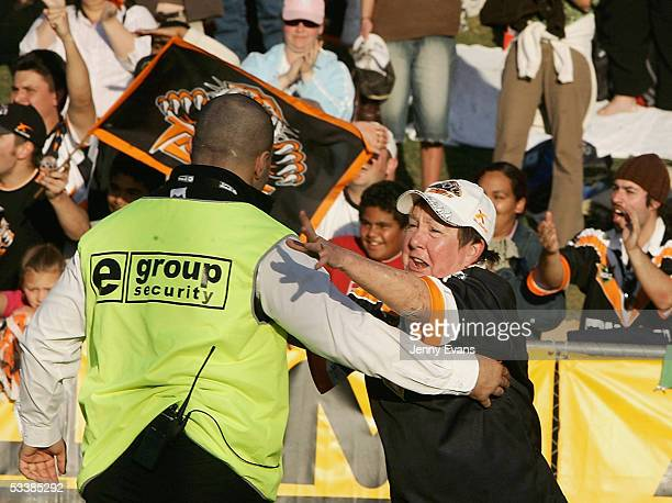 A security guard restrains a spectator after she ran onto the field after the Tigers won the round 23 NRL match between the Wests Tigers and the...