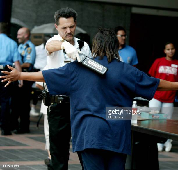 A security guard searches evacuees from New Orleans as they arrive at the George R Brown Convention Center September 3 2005 in Houston Texas