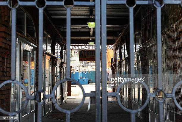 A security guard sits among empty stalls behind the locked gates of the Chirkizovsky market in Moscow on July 1 2009 The huge market that deals...