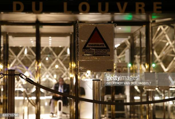 A security guard sits at the entrance of the Louvre Pyramid of the Louvre museum in Paris on February 3 as a sign with the symbol of France's...
