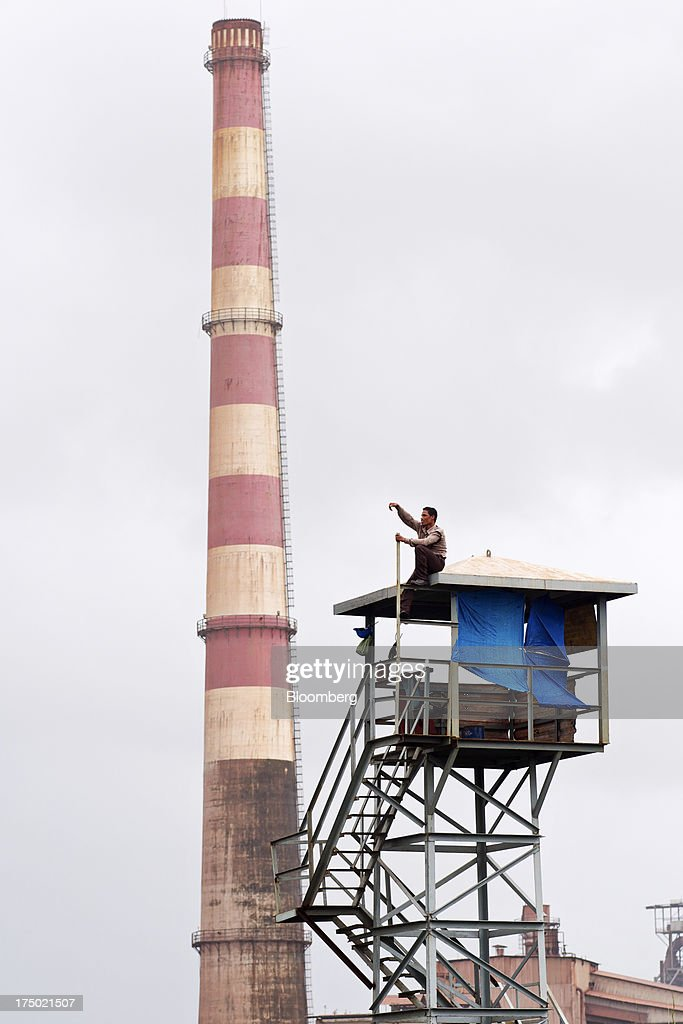 A security guard sits atop a watch tower at the JSW Steel Ltd. manufacturing facility in Dolvi, Maharashtra, India, on Friday, July 27, 2013. JSW Steel is scheduled to announce first-quarter earnings on July 31. Photographer: Adeel Halim/Bloomberg via Getty Images