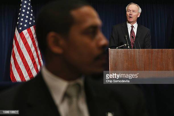 A security guard sits in front of former Drug Enforcement Administration Administrator and US Congressman Asa Hutchinson as he delivers remarks...