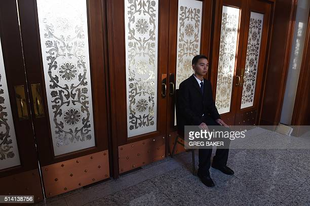 A security guard sits near a set of doors during delegation meetings at the National People's Congress in Beijing's Great Hall of the People on March...