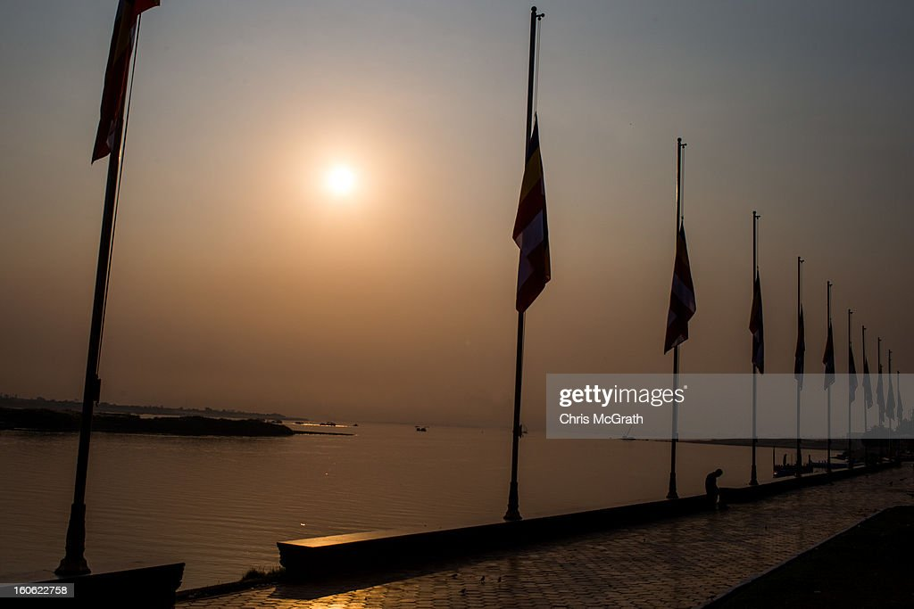 A security guard sits under flags at half mast for former King Norodom Sihanoukon on the riverfront at the Royal Palace February 4, 2013 in Phnom Penh, Cambodia. The former kings coffin was transported to the cremation site after being paraded through the capital in a lavish funeral procession. The cremation will take place on Monday evening the funeral pyre will be lit by his wife and son King Norodom Sihamoni.