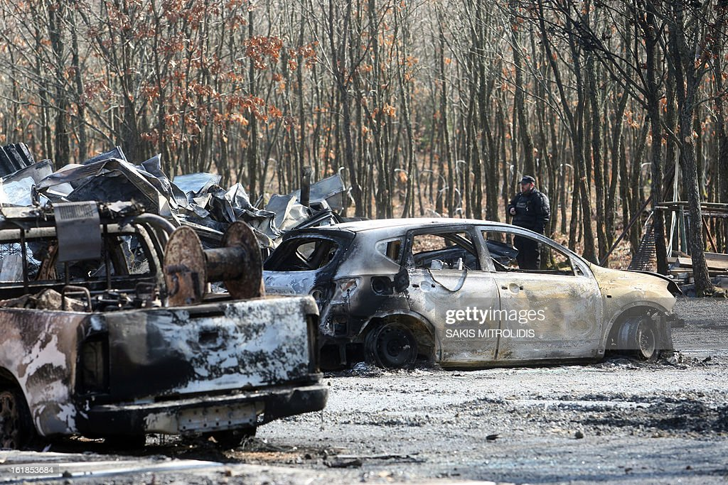 A security guard stands among burned-out cars on the Hellenic Gold site in the forest of Skouries, some 620kms north of Athens, on February 17, 2013. Dozens of hooded men firebombed the premises of a Greek subsidiary of a Canadian gold mining company today, injuring a guard and damaging containers, cars and trucks. The site has faced opposition from citizens' groups who fear the project will cause irreversible harm to the local environment. They have been trying to halt the project since 2011, when the Greek government allowed Hellenic Gold, a subsidiary of Canadian company Eldorado Gold, to dig in the region. AFP PHOTO /Sakis Mitrolidis