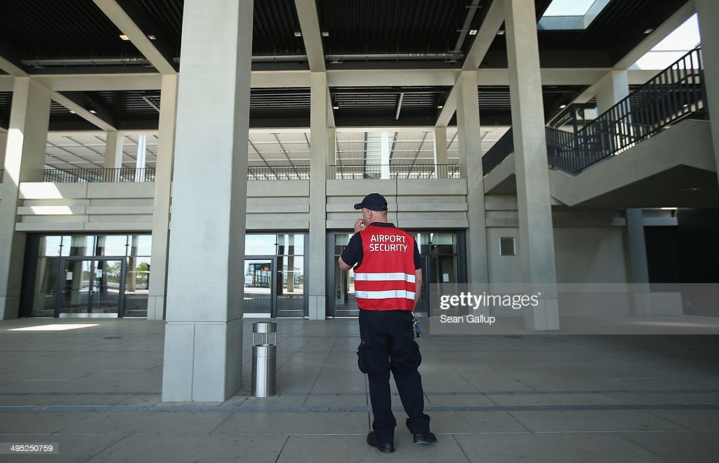 A security guard stands at the main terminal at the unfinished new BER Willy Brandt Berlin Brandenburg International Airport on June 2, 2014 in Schoenefeld, Germany. The airport, which is years behind schedule with no opening date yet in sight, has now been hit by a corruption scandal involving head technician Jochen Grossmann, who is accused of demanding a EUR 500,000 bribe from a contracting firm. The airport's governing body is meeting today and has designated a task force to determine whether Grossmnn might have demanded bribes from other companies as well.