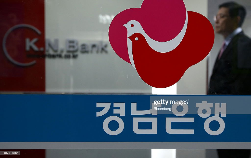 A security guard stands behind the logo for Kyongnam Bank, a unit of Woori Finance Holdings Co., displayed at one of the bank's branches in Seoul, South Korea, on Tuesday, Nov. 12, 2013. Woori Finance Holdings is scheduled to report third-quarter results on Nov. 14. Photographer: SeongJoon Cho/Bloomberg via Getty Images