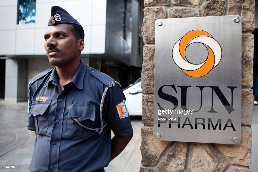 A security guard stands beside signage outside the Sun Pharmaceutical Industries Ltd. corporate office in the Andheri suburb of Mumbai, India, on Monday, April 7, 2014. Sun Pharmaceutical, India's largest drugmaker by market value, agreed to buy Ranbaxy Laboratories Ltd. for $3.2 billion in stock, the biggest purchase by an Indian company in two years. Photographer: Amit Madheshiya/Bloomberg via Getty Images