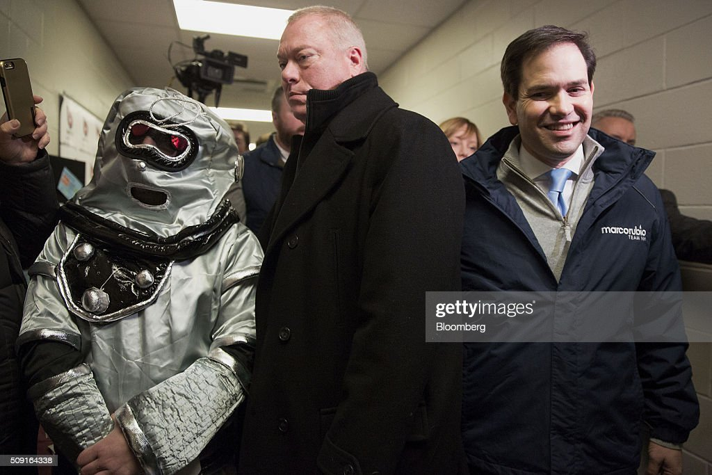 A security guard stands between Senator <a gi-track='captionPersonalityLinkClicked' href=/galleries/search?phrase=Marco+Rubio+-+Politician&family=editorial&specificpeople=11395287 ng-click='$event.stopPropagation()'>Marco Rubio</a>, a Republican from Florida and 2016 presidential candidate, right, and a man dressed as a robot during a visit to a polling station in Bedford, New Hampshire, U.S., on Tuesday, Feb. 9, 2016. Voters in New Hampshire took to the polls today in the nation's first primary in the U.S. presidential race. Photographer: Daniel Acker/Bloomberg via Getty Images