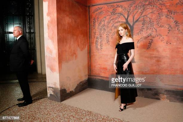 A security guard stands by as British actress Ellie Bamber poses during the photocall before the Chanel Croisiere fashion show on May 3 2017 at the...