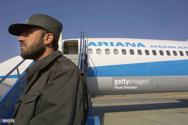 A security guard stands by in front of a 727 before its makes Ariana Afghan Airlines first international flight in five years January 24 2002 in...