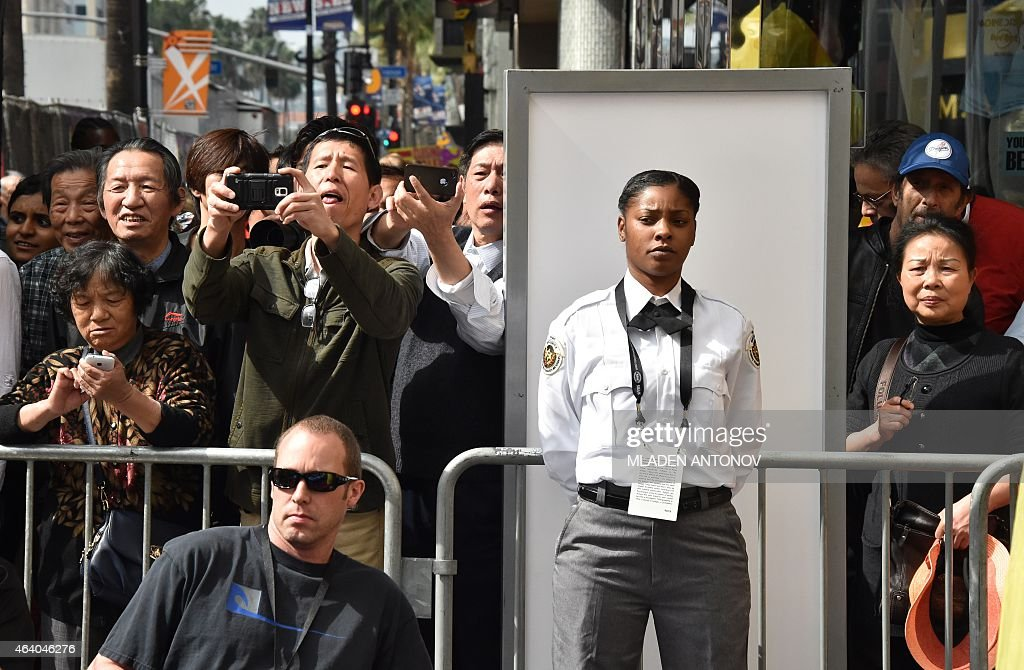 A security guard stands guard as tourists take photos of the red carpet outside the Dolby Theatre as preparations are underway for the 87th annual...