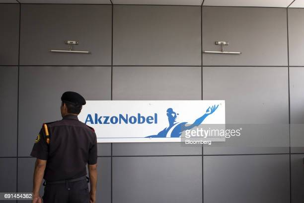 A security guard stands in front of signage for Akzo Nobel India Ltd at the company's factory in Gwalior Madhya Pradesh India on Thursday June 1 2017...