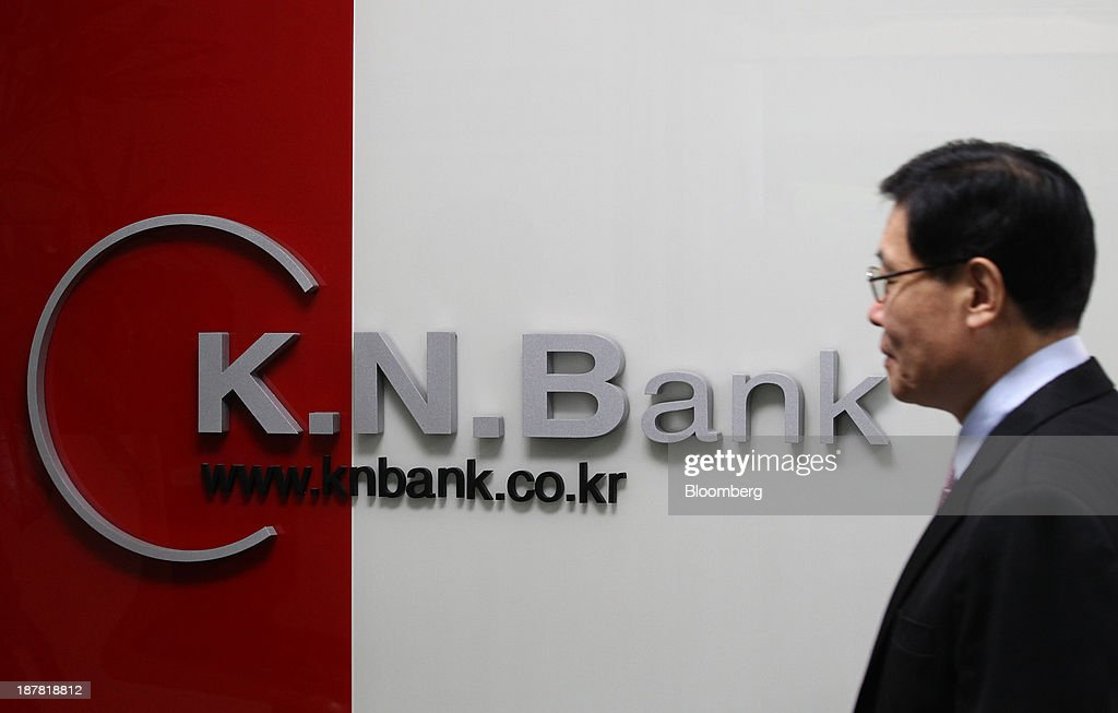 A security guard stands in front of signage for Kyongnam Bank, a unit of Woori Finance Holdings Co., displayed at one of the bank's branches in Seoul, South Korea, on Tuesday, Nov. 12, 2013. Woori Finance Holdings is scheduled to report third-quarter results on Nov. 14. Photographer: SeongJoon Cho/Bloomberg via Getty Images