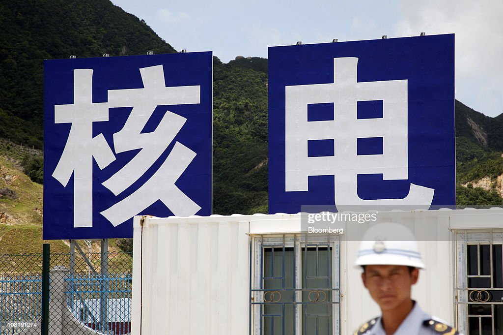 A security guard stands in front of signs displaying the Chinese characters reading 'nuclear power' at the China Guangdong Nuclear Power Group Co...