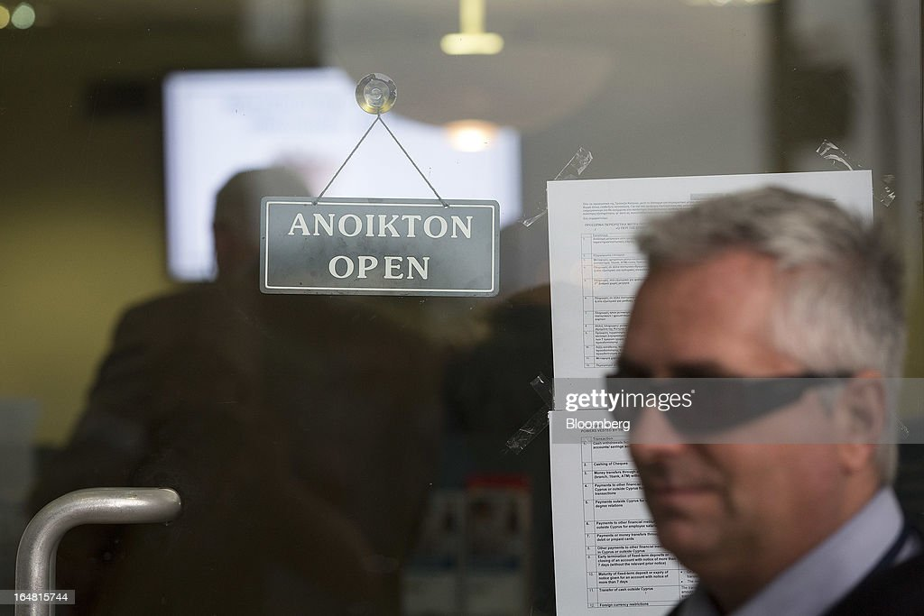 A G4S security guard stands in front of the door of a Bank of Cyprus Plc branch as banks open for the first time in two weeks in Nicosia, Cyprus, on Thursday, March 28, 2013. The Central Bank of Cyprus's capital controls will include a 300-euro ($383) daily limit on withdrawals and restrictions on transfers to accounts outside the country. Photographer: Simon Dawson/Bloomberg via Getty Images