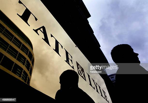 A security guard stands in the front of the logo of Tate Lyle on the fascade of the company's office building on Lower Thames Street London