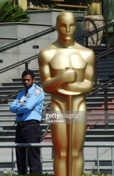 A security guard stands near an Oscar statue outside the Kodak Theater at the 75th Academy Awards show March 23 2003 in Hollywood California Security...