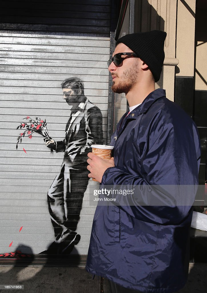 A security guard stands near graffiti by British street artist Banksy painted on a roll-down security gate covering the main entrance to Larry Flint's Hustler Club on October 24, 2013 in the Hell's Kitchen neighborhood of New York City. On Banksy's website a caption for the work reads, 'Waiting in vain...at the door of the club.'