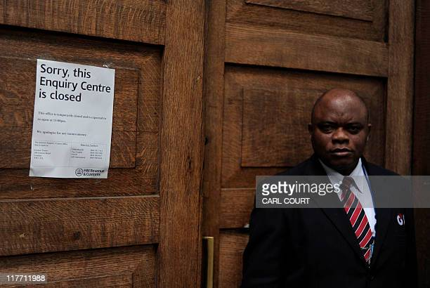 A security guard stands next to a 'closed' notice on the door of a HMRC building in central London on June 30 2011 Hundreds of thousands of British...