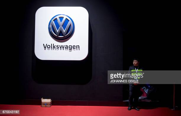 A security guard stands next to a logo of German car maker VW Volkswagen during the media day of the 17th Shanghai International Automobile Industry...