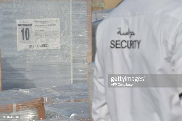 A security guard stands next to ballots for Kenya's upcoming presidential elections before before their shipment on October 21 at a printing and...