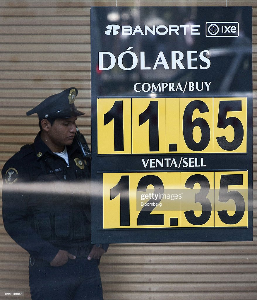 A security guard stands next to the currency exchange display rate sign at Banorte bank at Avenue Reforma in Mexico City, Mexico, on Tuesday, April 9, 2013. Mexico's peso rose to the strongest since August 2011 after a report showed faster-than-forecast inflation last month, damping speculation that policy makers will cut interest rates to slow the currency's advance. Photographer: Susana Gonzalez/Bloomberg via Getty Images