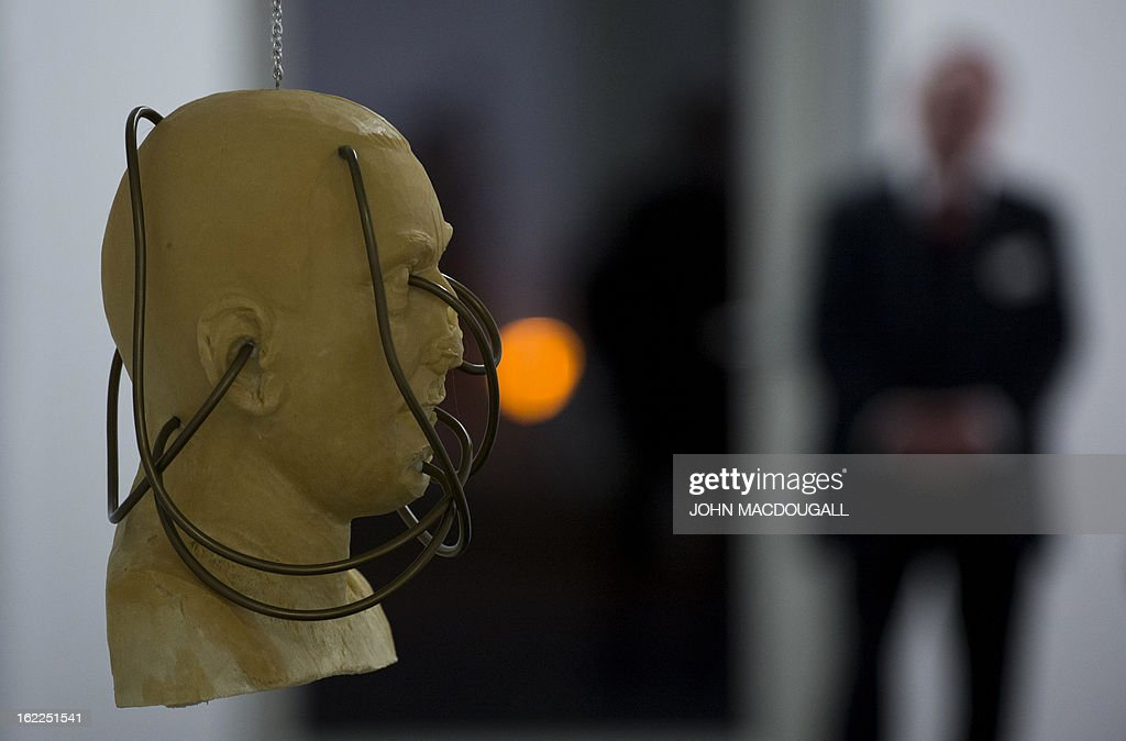A security guard stands next to the sculpture of a head pierced by thick wires (untitled and undated) by German artist Martin Kippenberger (1953-1997), on display at the exhibition 'Martin Kippenberger Sehr Gut / Very Good' at Berlin's Hamburger Bahnhof museum for contemporary art on February 21, 2013. The exhibition, a retrospective of the artist's prolific and varied output opens from February 23 to August 18, 2013.